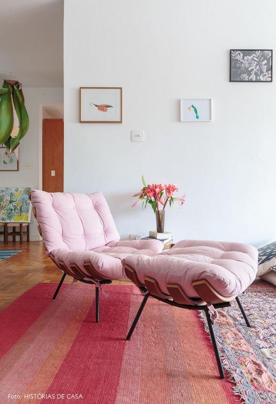Poltrona rosa com puff capitonê na sala de estar