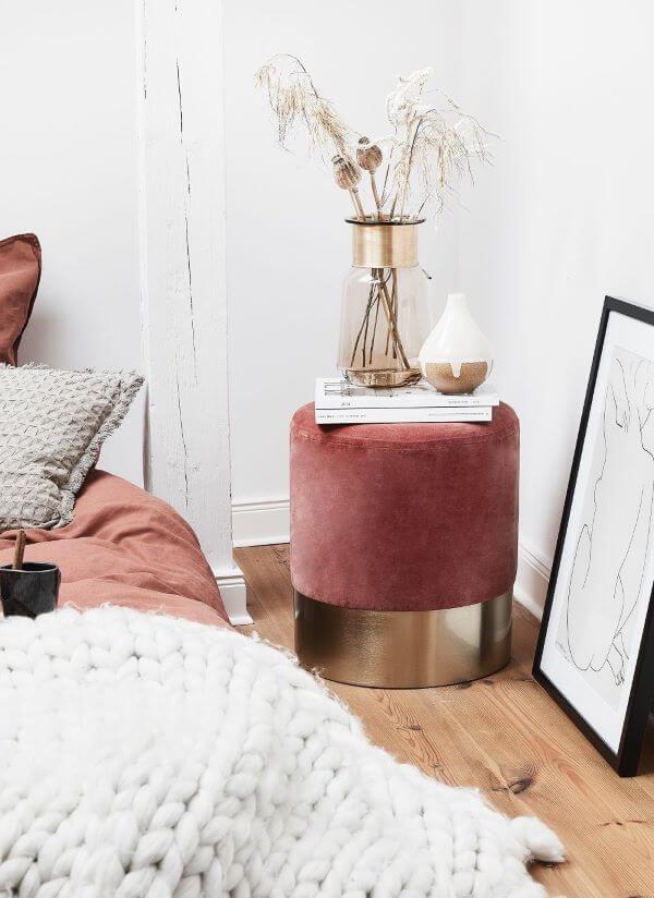 Puff rosa com dourado ao lado da cama