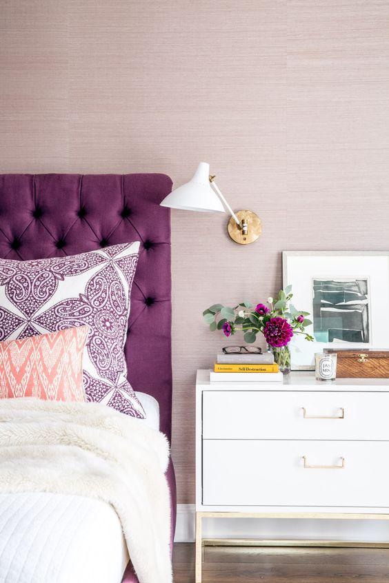Cabeceira roxa com móveis brancos em destaque