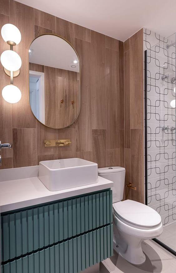 Banheiro com revestimento amadeirado e gabinete verde