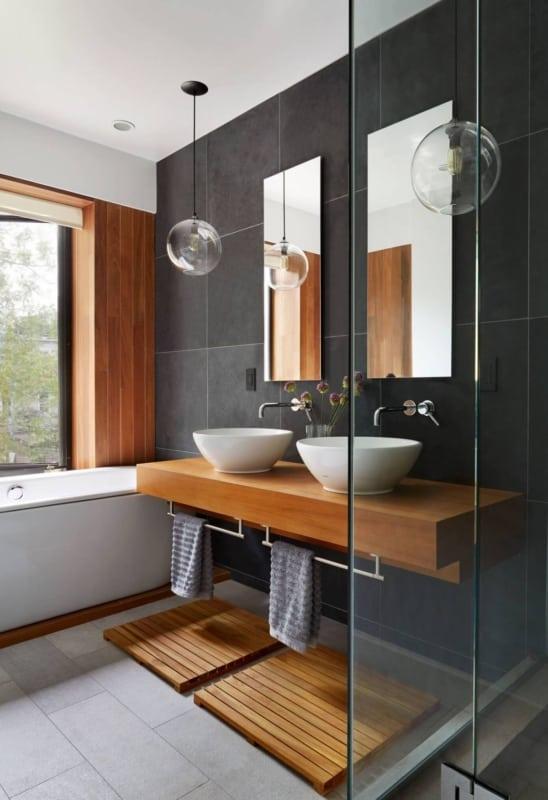 Banheiro preto com revestimento de madeira na parede