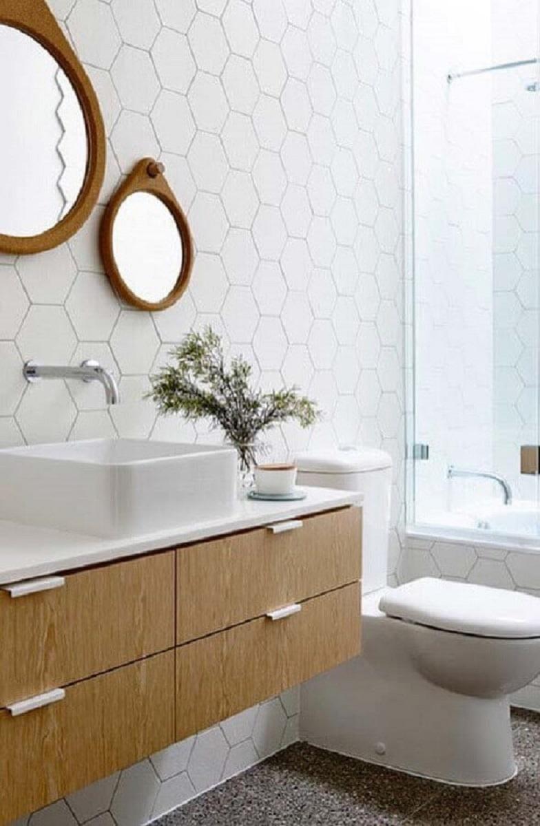revestimento hexagonal branco decorado com espelhos redondos e gabinete de madeira suspenso Foto Apartment Therapy