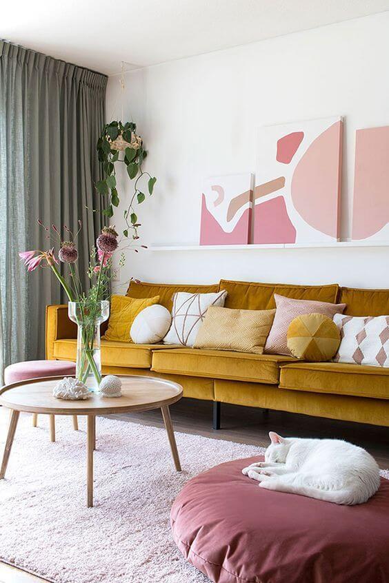 Sala de estar aconchegante com sofá amarelo mostarda e puff