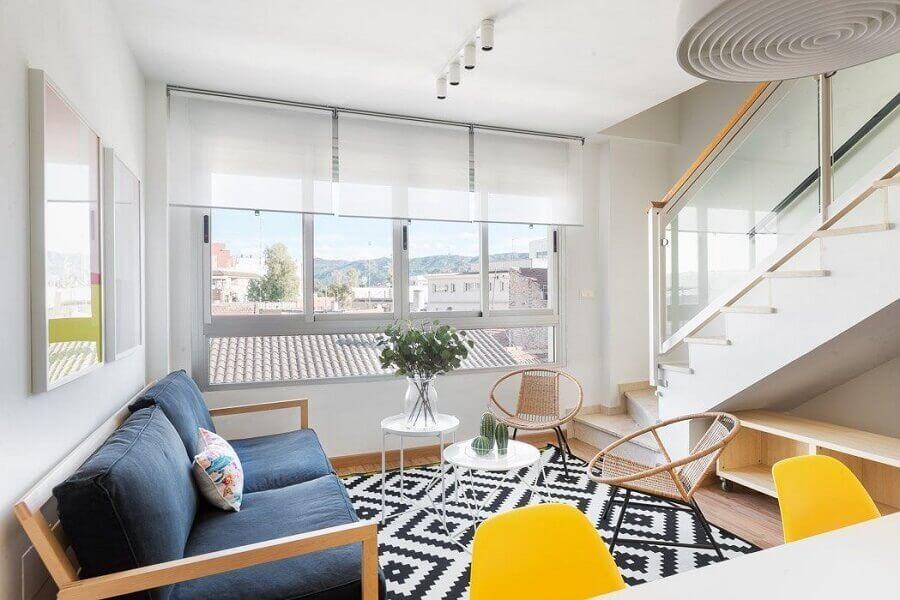 sala branca decorada com tapete geométrico e sofá de madeira azul escuro - Foto habitissimo