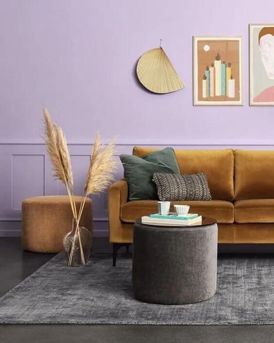 Sala com sofá mostarda e cor de tinta lavanda na parede
