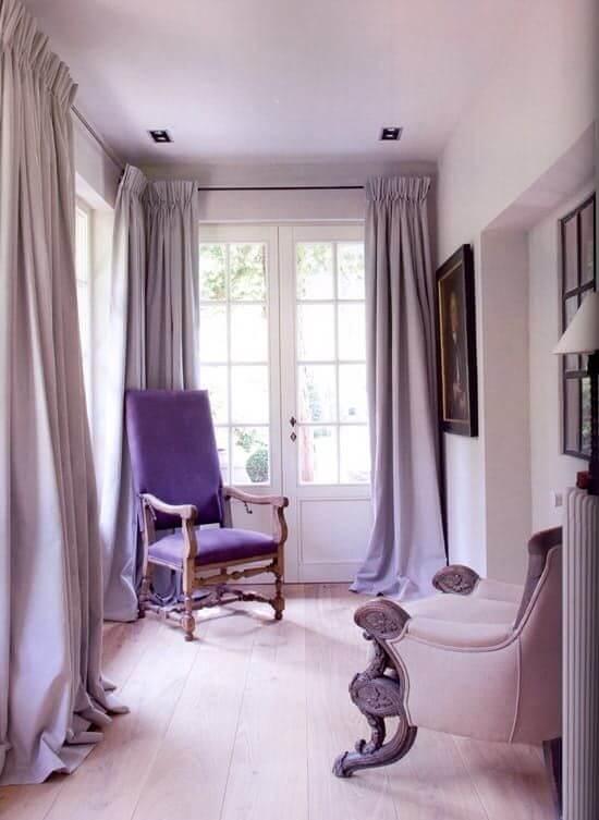 Sala na cor lavanda com cortinas e poltronas na tonalidade