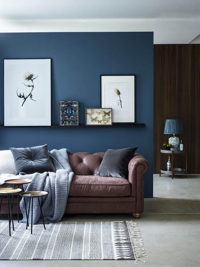 sala de estar decorada com parede na cor azul escuro e sofá marrom  Foto La Maison Jolie