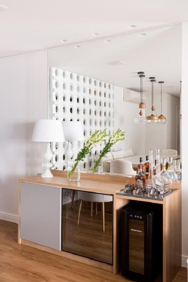 sala de jantar branca decorada com armário buffet pequeno de madeira planejado com espaço para frigobar Foto Jeito de Casa