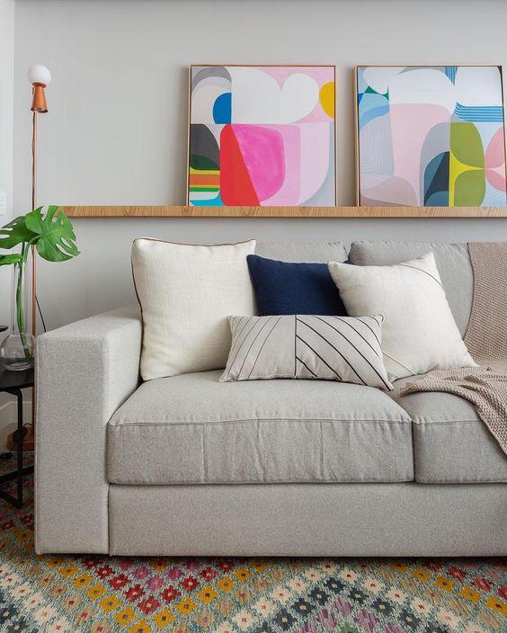 Sala com sofá simples e prateleira de quadros coloridos