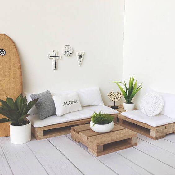 Sofá de canto feito de palete com almofadas brancas