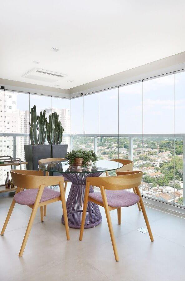 varanda de apartamento decorada com mesa redonda de vidro e cadeiras de madeira Foto Karen Pisacane