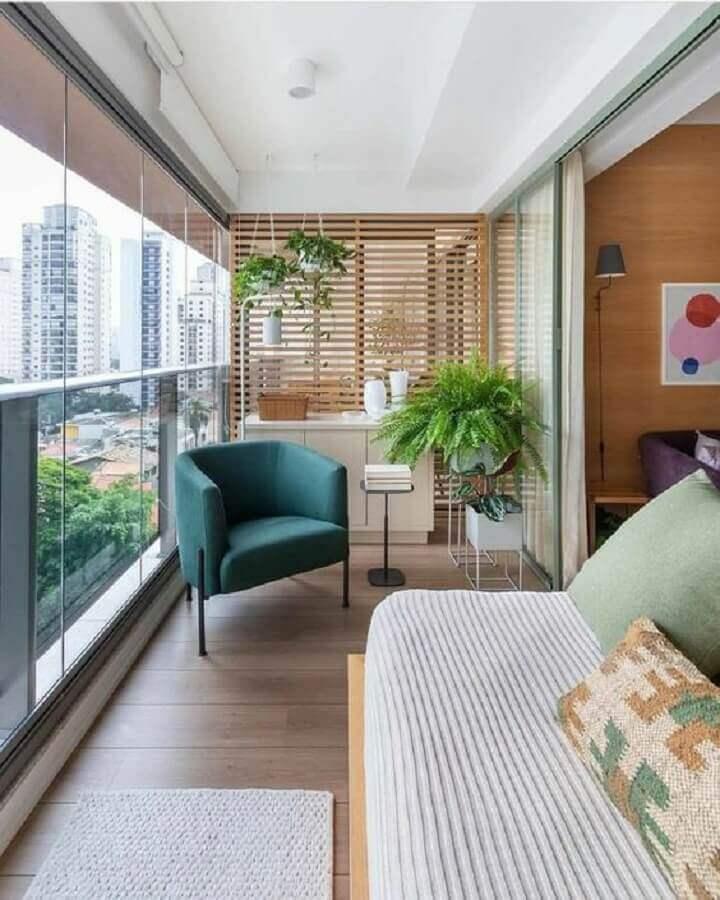 varanda de apartamento decorada com vasos de plantas e poltrona confortável  Foto Carol Mendonça