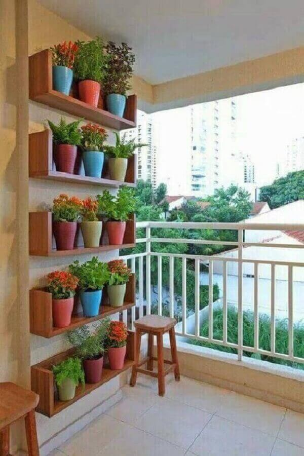 varanda de apartamento pequeno decorado com jardim vertical feito com vasos em prateleiras de madeira Foto Pinterest