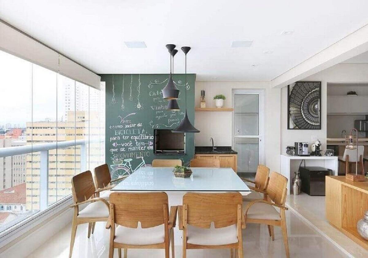varanda gourmet de apartamento decorada com mesa quadrada e churrasqueira com parede de tinta lousa  Foto Renata Cafaro