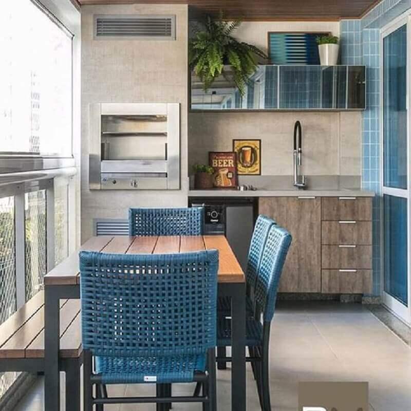 varanda gourmet pequena apartamento decorado com móveis de madeira e cadeiras azuis Foto Arkpad