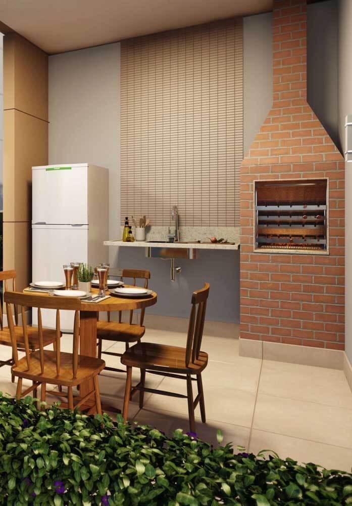 Área social com churrasqueira de tijolinho pequena e pia ao lado