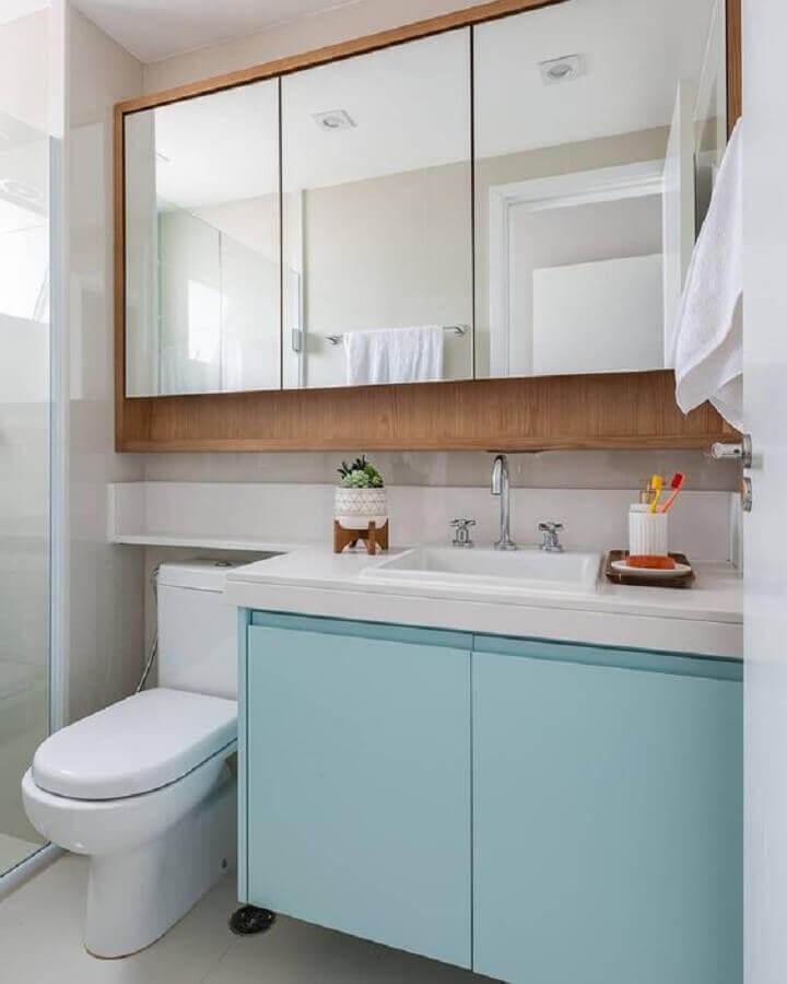 Decoração com espelheira de madeira e armario de banheiro pequeno azul claro e branco