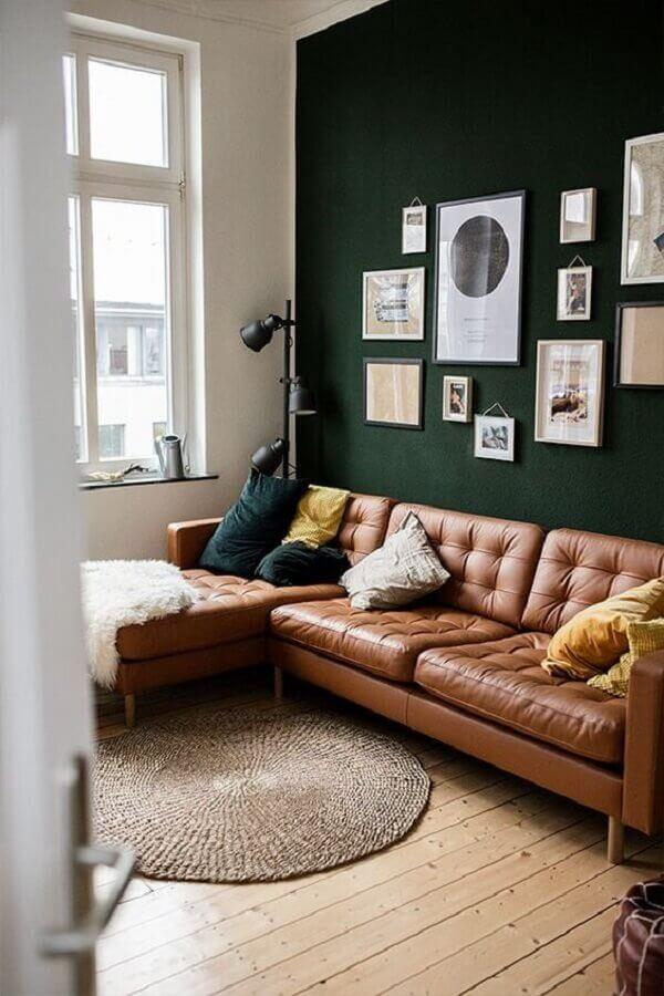 Parede cor verde escuro para sala de estar decorada com sofá de couro marrom com chaise