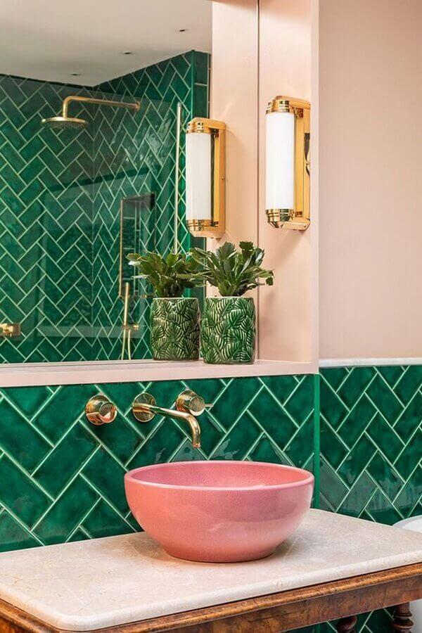 Decoração de banheiro com cuba cor de rosa e revestimento de parede na cor verde escuro