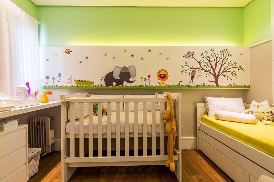 Decoração de quarto de bebê com parede cor verde claro e adesivos de animaizinhos