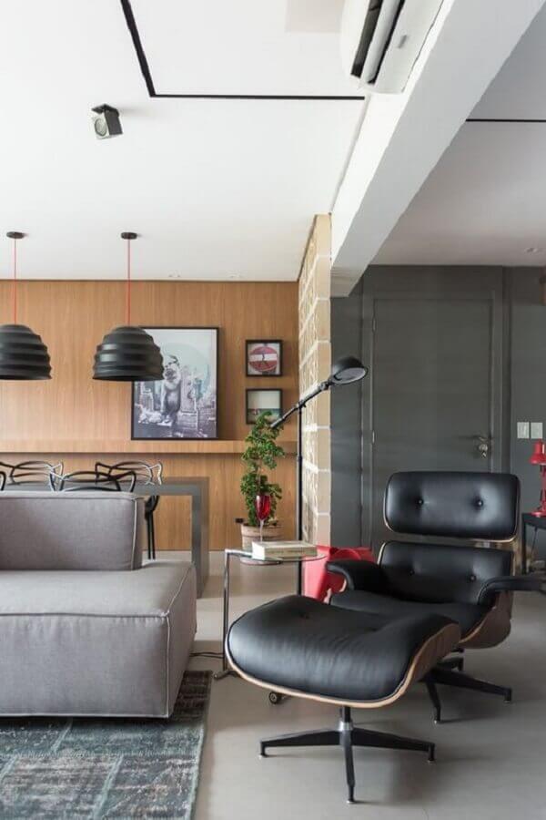 Sala moderna decorada com poltrona preta com puff confortável