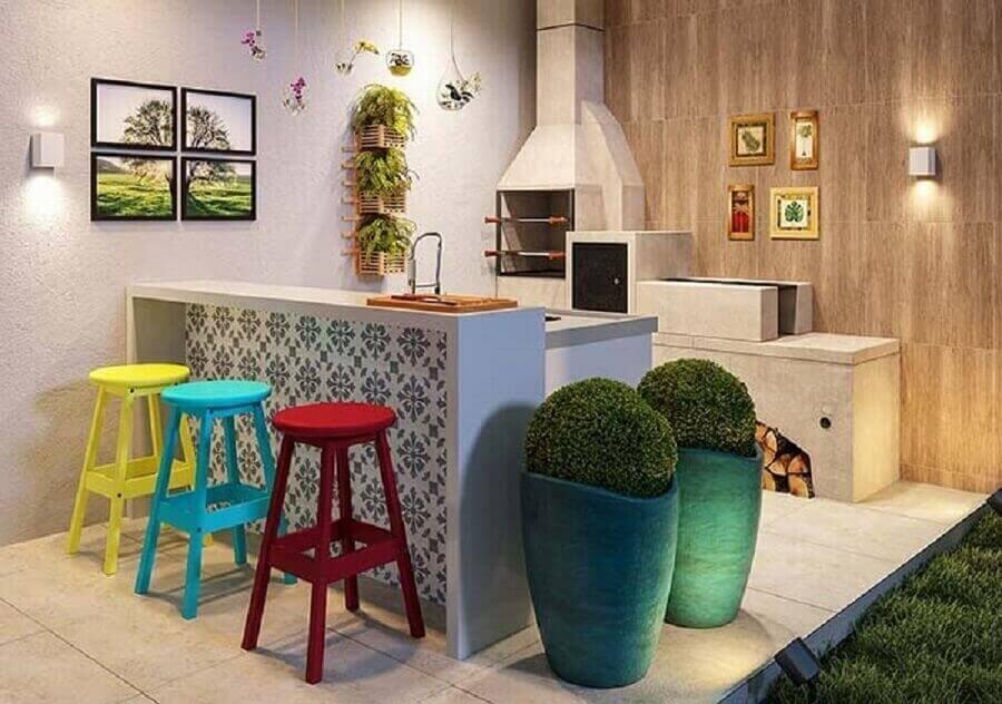 Área gourmet simples decorada com banquetas para bancada coloridas