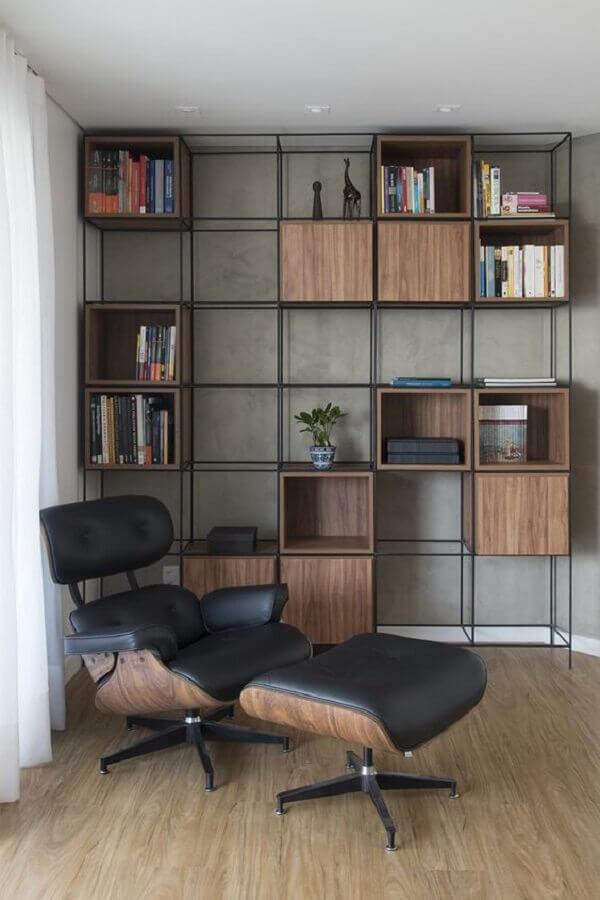 Decoração de sala com poltrona preta com puff e estante estilo industrial