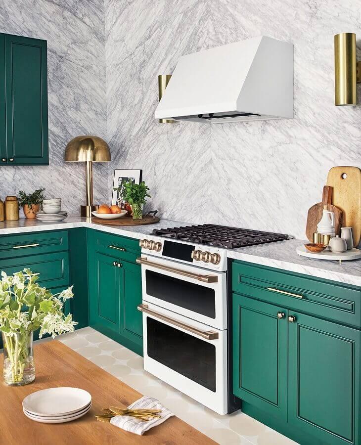 Decoração de cozinha com revestimento de mármore e armário planejado na cor verde esmeralda com puxadores dourados