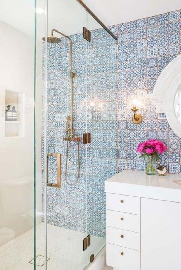 A bancada branca traz neutralidade para o banheiro com azulejos portugueses antigos