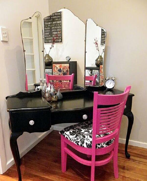 A cadeira rosa quebra a sobriedade da penteadeira preta com espelho