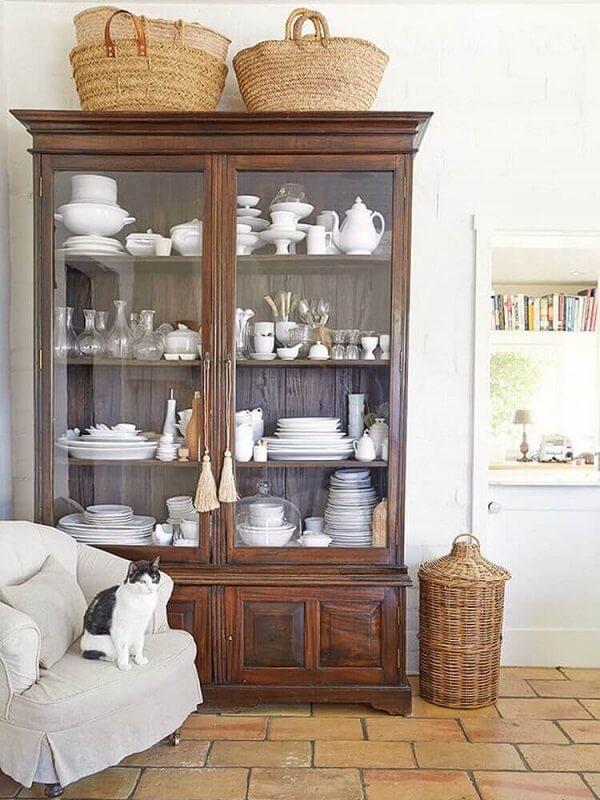 A cristaleira de madeira rustica acomoda vários itens de cozinha em seu interior
