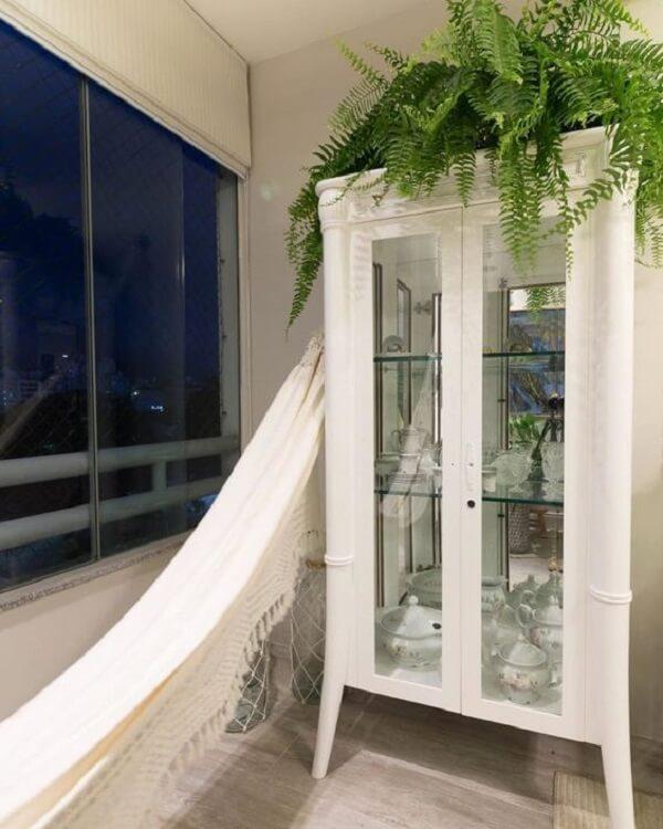 A cristaleira rústica branca divide espaço com a rede de descanso na varanda