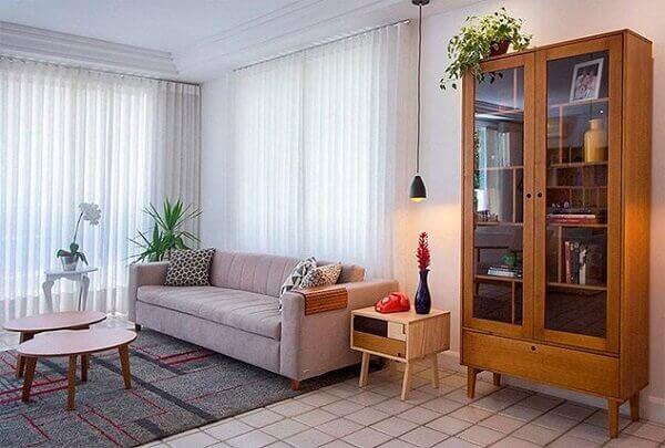 A cristaleira rústica complementa a decoração da sala de estar
