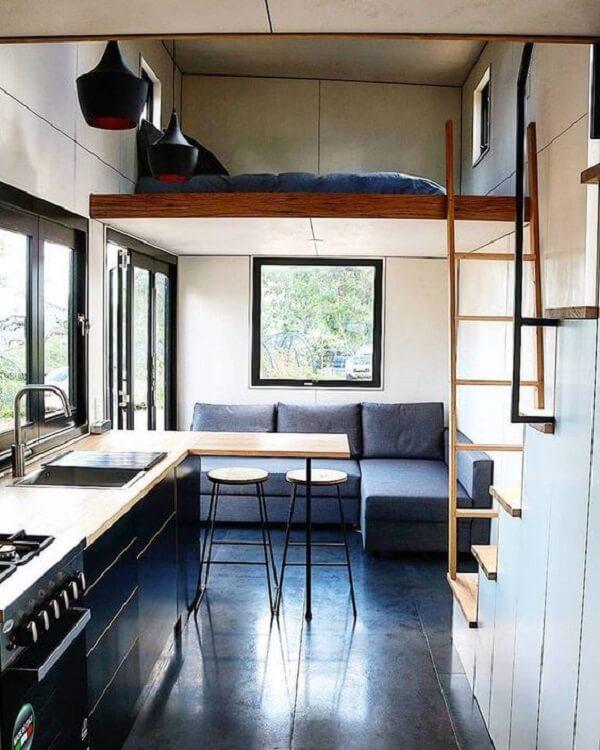 A escada discreta de madeira leva até a cama mezanino de casal