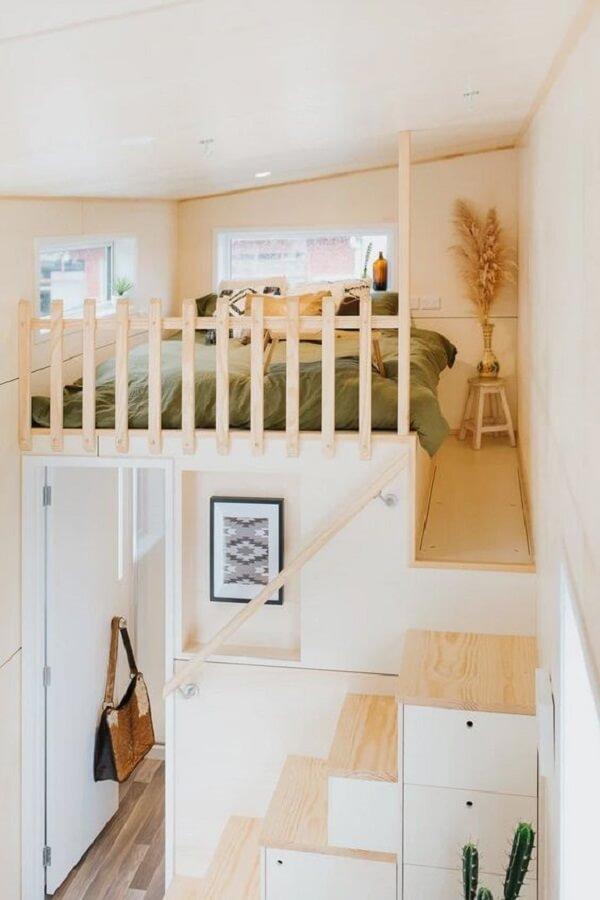 A escada funcional repleta de compartimentos conduz os moradores até a cama mezanino casal