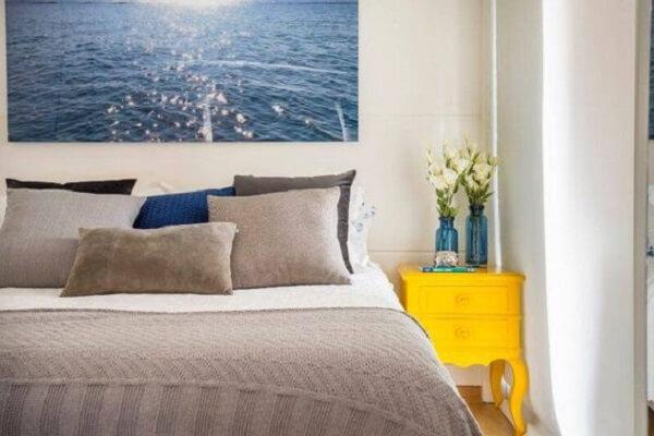 A mesa de cabeceira retrô amarela ilumina a decoração do quarto