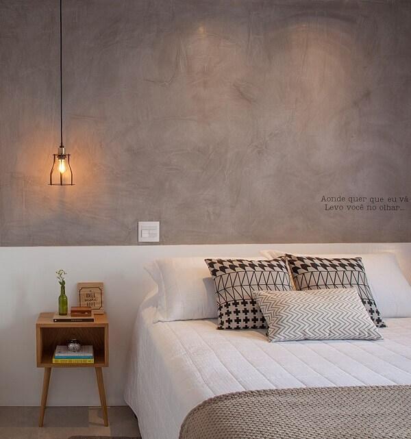 A parede de cimento queimado e a mesa de cabeceira retrô trazem personalidade para o quarto