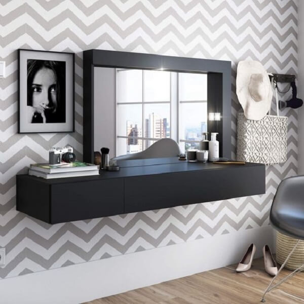 A penteadeira suspensa preta se destaca do papel de parede
