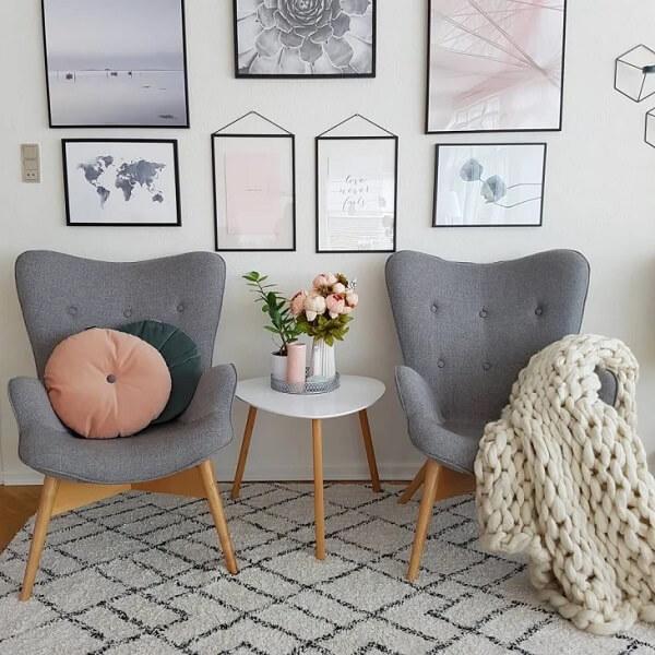 A poltrona pé palito cinza se conecta com a mesa de centro da sala