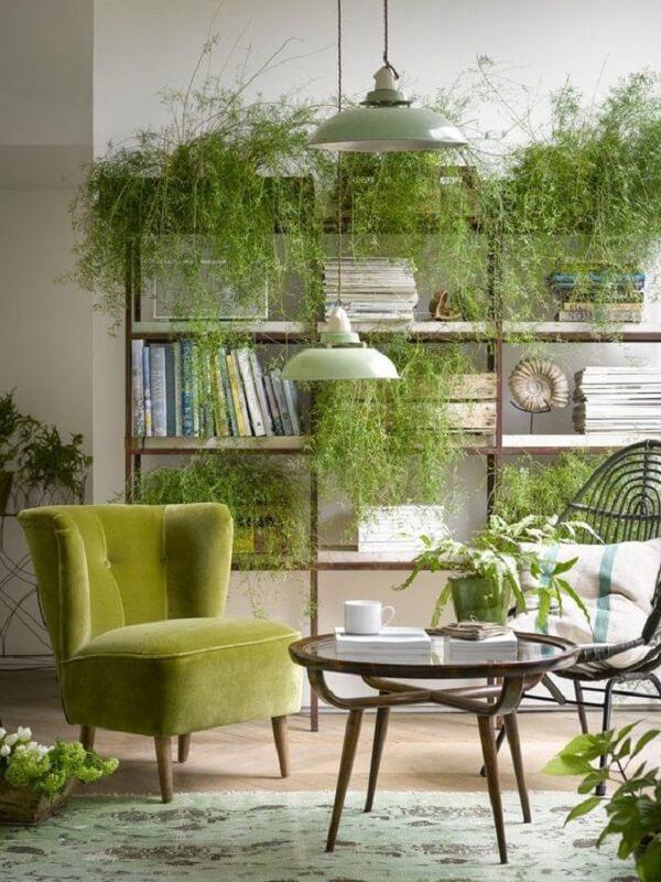 A poltrona pé palito verde se mistura em meio as plantas da sala de estar