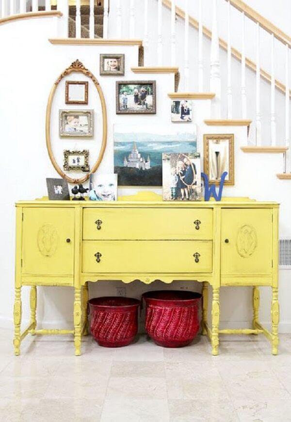 Acomode vários porta retratos sobre o aparador amarelo