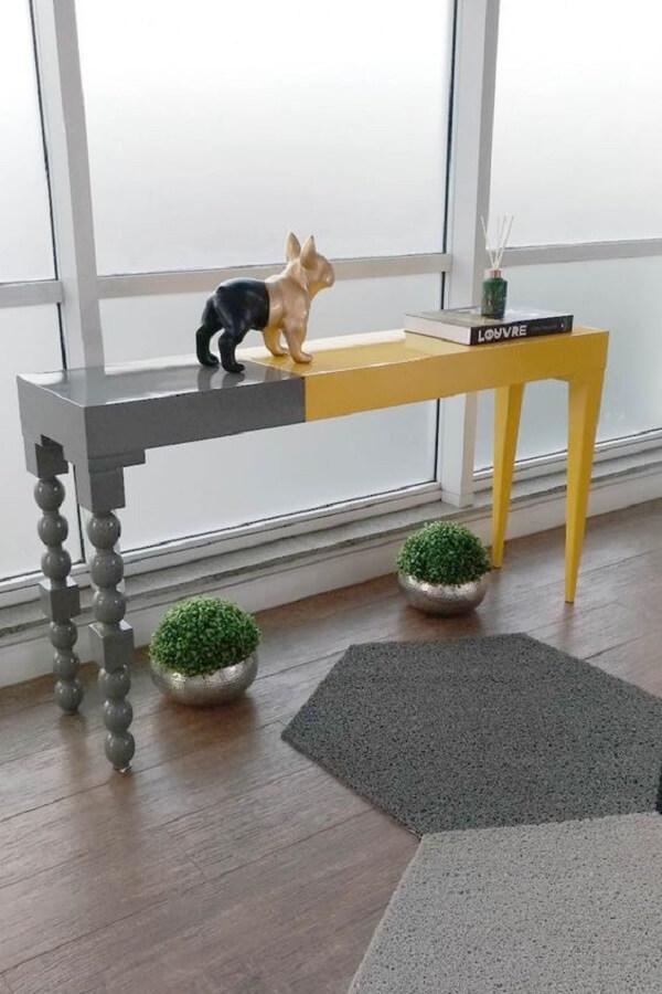 Aparador amarelo e cinza decoram o hall de entrada