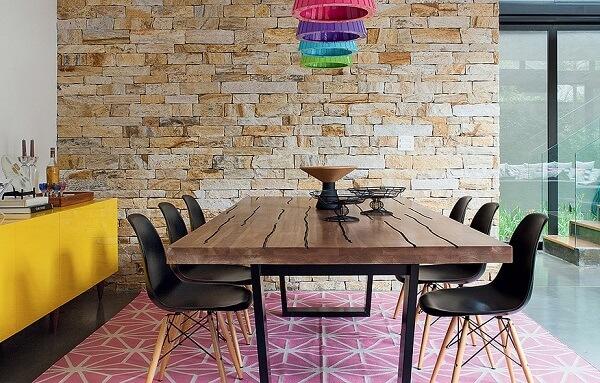 Aparador amarelo, tapete rosa e pendentes coloridos trazem alegria para a sala de jantar