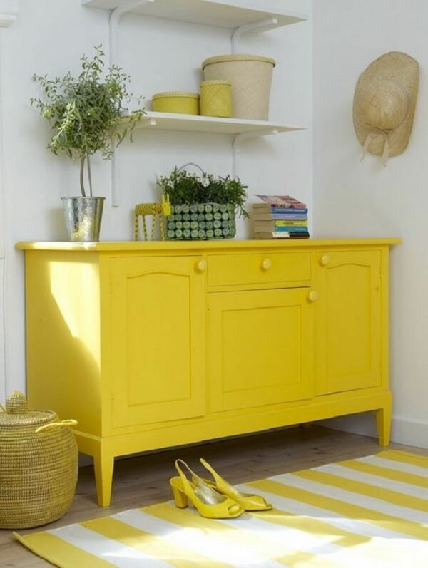 As gavetas e portas do aparador amarelo são usadas para guardar acessórios dos moradores