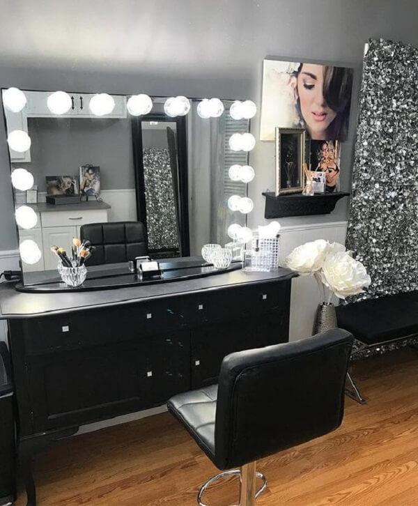 As lâmpadas de Led ao redor do espelho trazem charme para a estrutura da penteadeira preta