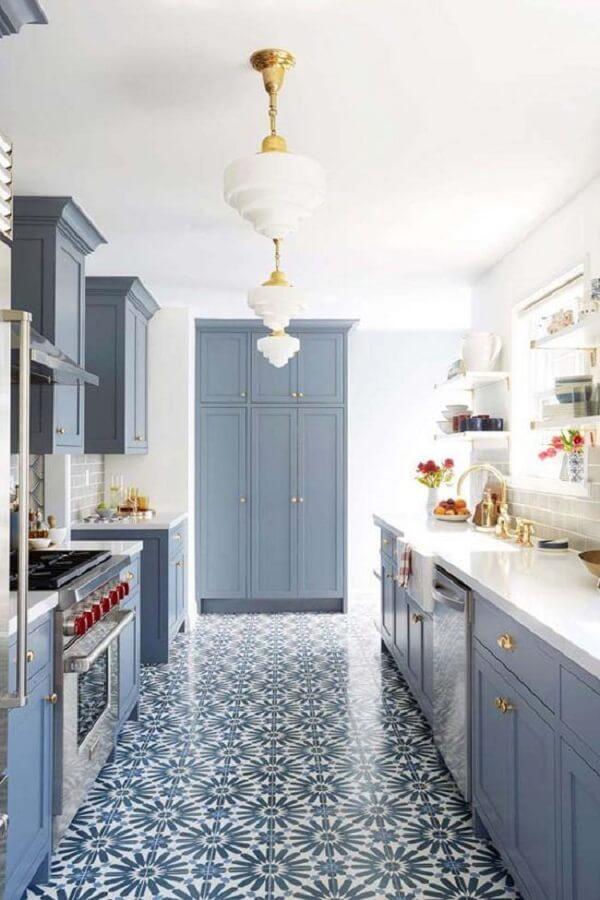 Azulejo antigo português no chão e móveis em tom azul suave decoram a cozinha