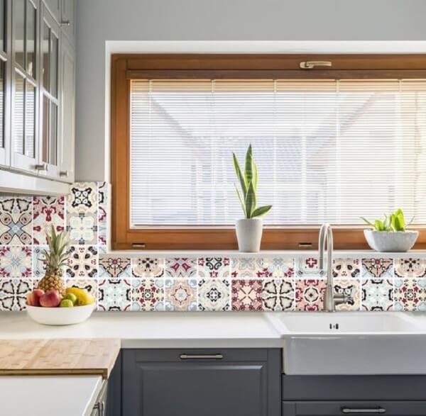 Azulejos antigos com diferentes estampas em tons de vinho, azule bege decoram a cozinha