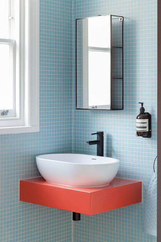 Banheiro azul com bancada coral