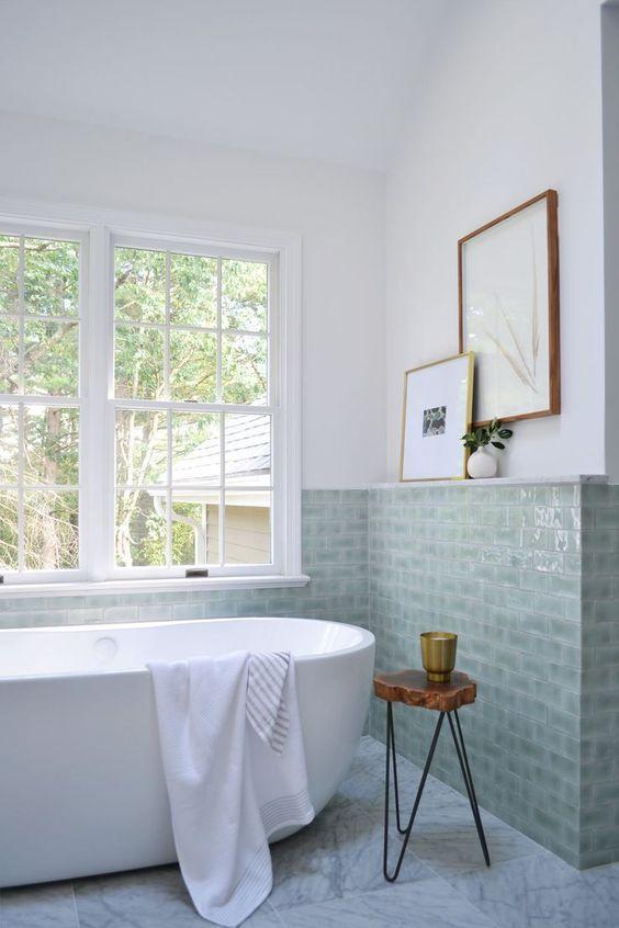 Banheiro com banheira e revestimento verde claro
