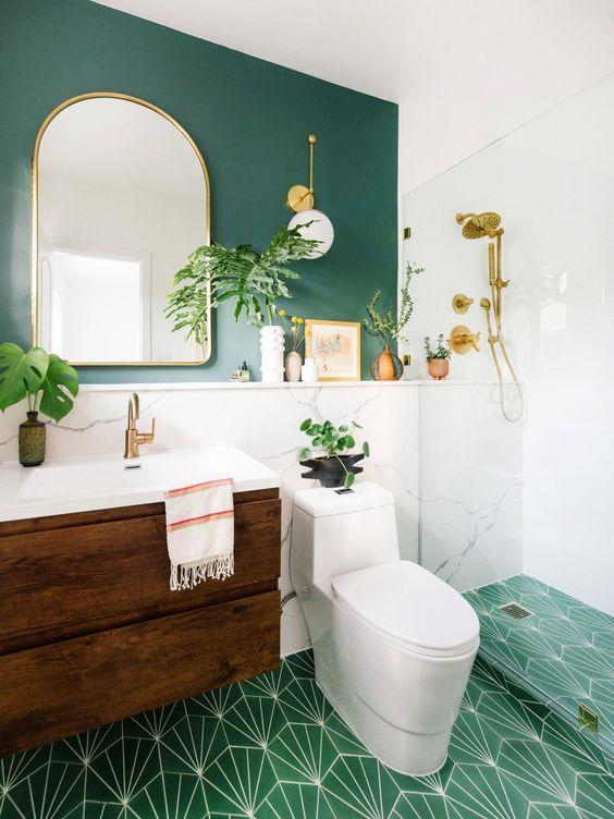 Banheiro com parede verde e piso branco e verde